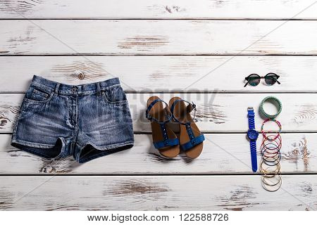 Woman's stylish shorts and footwear. Vintage showcase with clothes. Footwear, shorts and accessories. Lady's shoes and shorts.