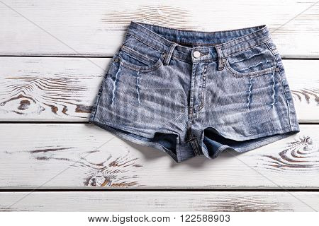 Female vintage denim shorts. Shorts on white wooden background. Simple denim shorts for women. Classic denim garment.
