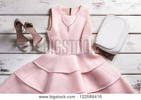 Dress and accessories on showcase. Stylish outfit on wooden background. Garment of evening collection. Warm-colored dress and jewelry.