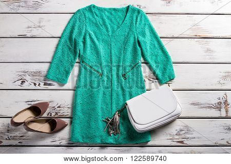 Turquoise dress and white purse. Female outfit on white shelf. Leather clutch purse and dress. Elegant garment and heel shoes.