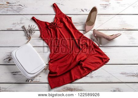Red dress with clutch bag. Clothes and footwear on table. Fashionable garments for modern women. City girl's outfit.