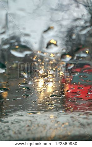 road and cars through wet windshield at rain