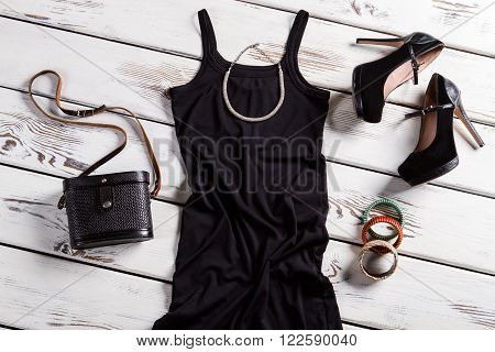 Black dress and small necklace. Jewelry and clothes on shelf. Frosted heel shoes and accessories. Suede shoes and retro purse.