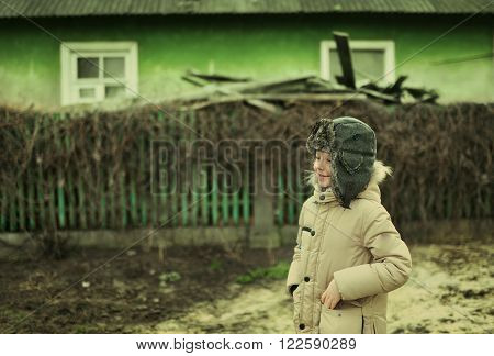 in the village at the house with a fence cheerful little boy in a jacket and hat with earflaps
