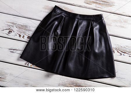 Black leather skirt with folds. Leather skirt on wooden background. Merchandise at a nice discount. New clothes from city shop.