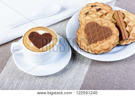 A cup of cappuccino latte drawing heart shaped cookies with cinnamon picture of a heart-shaped white cloth ceramic spoon on a coarse fabric tablecloth.