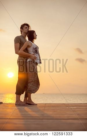 Embracing couple in aladdin trousers on the tropical sunset background