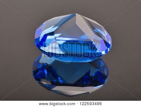 blue sapphire with reflection on dark brown background
