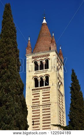 Detail of the beautiful romanesque San Zeno Basilica in Verona with its conical brick spire between two cypress