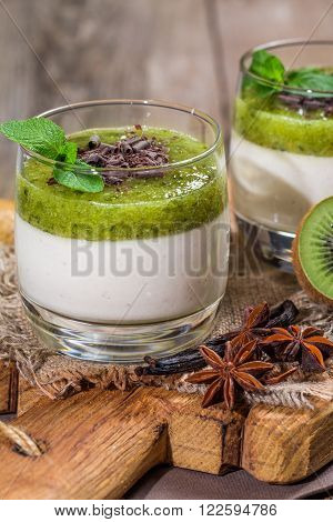 Fruit dessert green panna cotta with mint in a glass over wooden background
