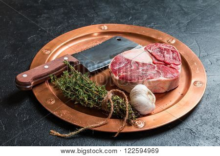Raw veal shank slices meat and ingredients for Osso Buco cooking on black background top view