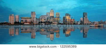 Canary Wharf business district in London at sunset with reflection.