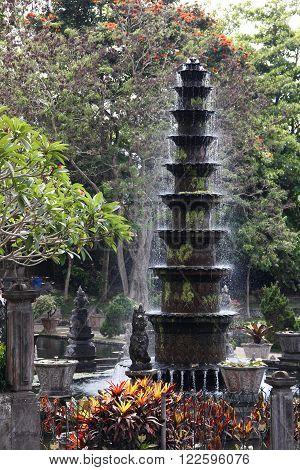 Spouting Fountain with sparkling drops of water in Bali water palace gardens of Tirtagangga temple. Traditional Balinese sculpture and architecture elements.