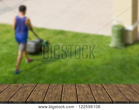 worker use lawnmower to trim grass lawn (blur background with wood table top for display or montage your product)