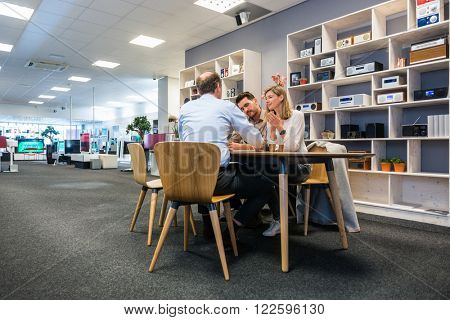 Salesman assisting young couple at counter in electronics shop