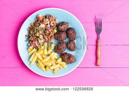Plate of fresh homemade spicy traditional Turkish kofta meatballs served with a fresh lentil salad and fried potato chips served on a vibrant pink picnic table overhead view