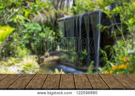 the man made waterfall in the botanical garden (blur background with wood table top for display or montage your product)
