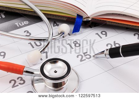 Close Up Of Stethoscope And Pen On Calendar, Doctor Appointment.