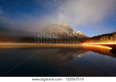Foggy mountain at night over lake with stars and traffic light trail in Banff National Park, Canada