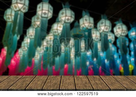 light of decorating paper lantern at Night in Yeepeng festival which is thailand tradition (blur background with wood table top for display or montage your product)