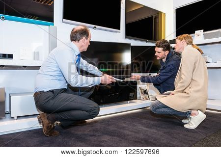 Mature assistant showing flat screen TV to couple in electronics section of hypermarket