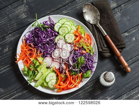 Fresh vegetable salad with red cabbage cucumber radish carrots sweet peppers red onion and parsley on a white plate. On wooden rustic background