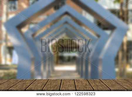 the design of gray modern archway in front of building (blur background with wood table top for display or montage your product)