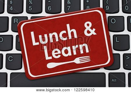 Lunch and Learn Sign A red hanging sign with text Lunch and Learn and a fork on a keyboard