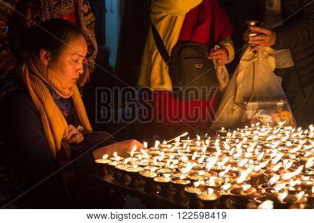 Kathmandu, Nepal - December 06, 2014: Pilgrims at Boudhanath stupa lighting up butter candles for full moon festival.