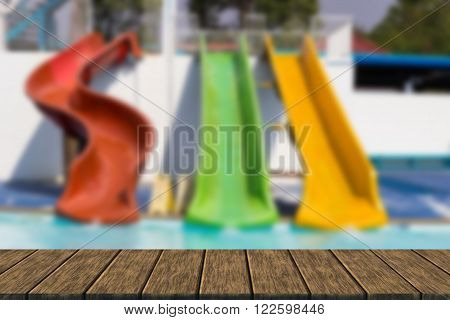 colorful slider beside swimming pool in water park (blur background with wood table top for display or montage your product)