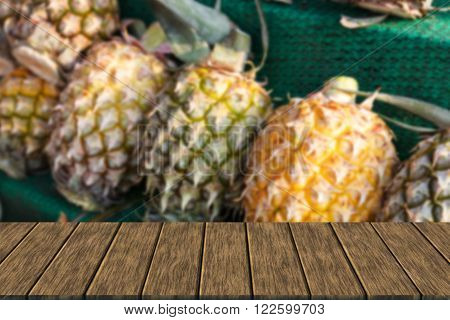 row of pineapple on shelf for sale at the market (blur background with wood table top for display or montage your product)