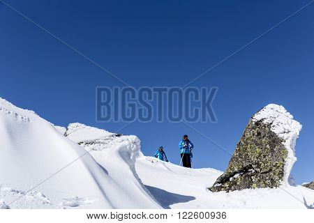 Sofia Bulgaria - March 12 2016: Two free riders are prepairing for skiing down a snowy rocky mountain top. During a bright sunny day. Clear blue sky.