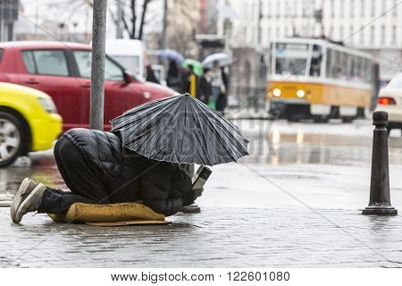 Beggar In The Rain With Umbrella Traffic
