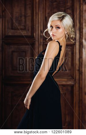 Young beautiful sexy woman in a luxury long elegant black dress, a trendy makeup and stylish earrings. Seductive blonde in a luxurious mansion, in vintage style, posing for the camera