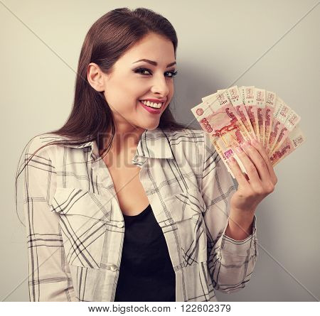 Happy Young Casual Woman Holding Rubles With Toothy Smiling. Toned Portrait
