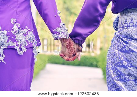 Closeup Malay Wedding Couple Holding Hands In Park.