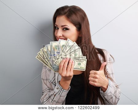 Happy Young Casual Woman Holding Dollars And Showing Thumb Up Sign On Blue Background