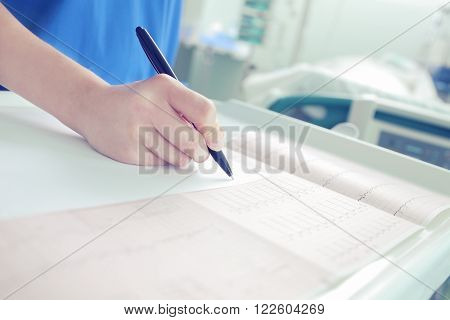 Doctor works with the medical test results in the ICU room.