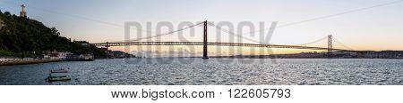 Panorama of Lisbon cityscape with 25 de Abril suspension Bridge, Portugal at dusk
