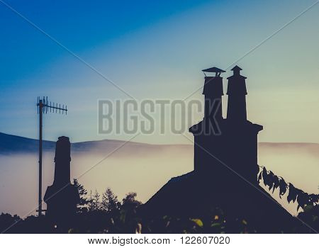Rural Rooftop And Chimney Against Misty Dusk With Copy Space