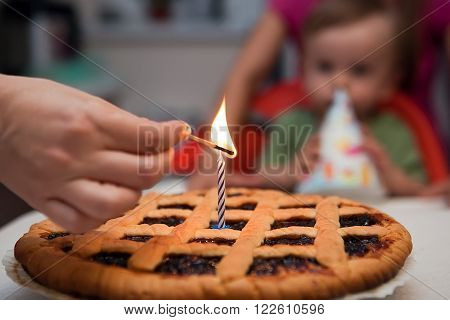 the concept of the first birthday of the child - mom's hand lights a candle on the cake