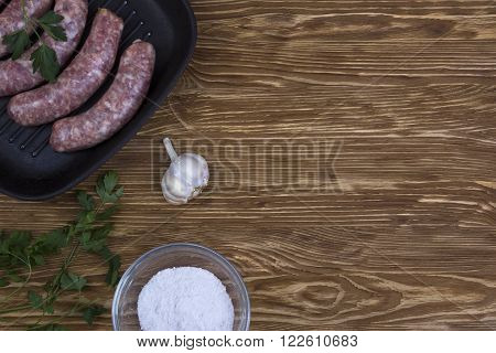 raw sausages on a  pan, salt and garlic on wooden background