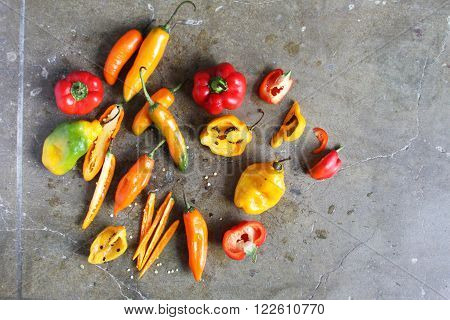 Overhead view of many whole and sliced colorful chili peppers on a stone slab