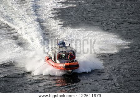 Ketchikan Alaska USA - June 13 2013: US Coast Guard 25-foot Defender-Class boat escorts a cruise ship out of Ketchikan