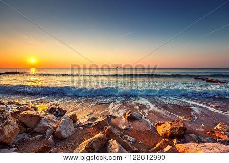 Beautiful Sunrise over the sea and sailing cargo ship