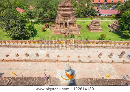 Top view on white buddha statue and small statue of monks in Wat Yai Chaimongkol of Ayutthaya Thailand. With background of pagodas in the green field.