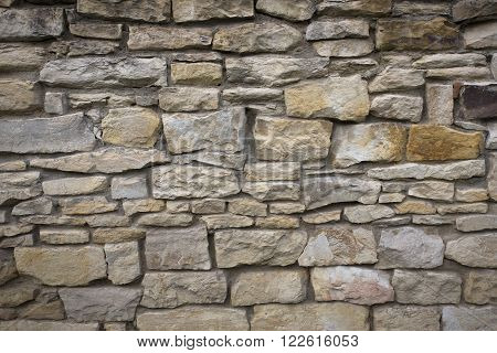 Stone old wall texture. Old rock blocks in old medieval brick. Exterior historical country situation with fencing. Village rural foundation background.