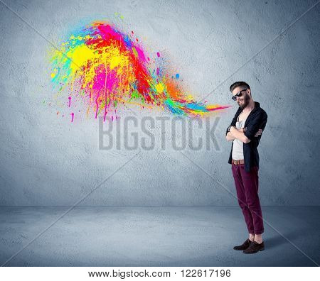 A funny hipster person in casual urban clothing shouting bright colorful paint on city wall concept