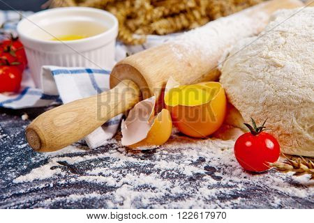 Baking background with eggshell, flour and rolling pin. Pizza cooking ingredients. Selective focus.