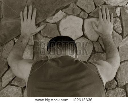 white man standing with his back having rested hands against a wall of stone. black and white toning shallow depth of field. the concept of police searches arrest